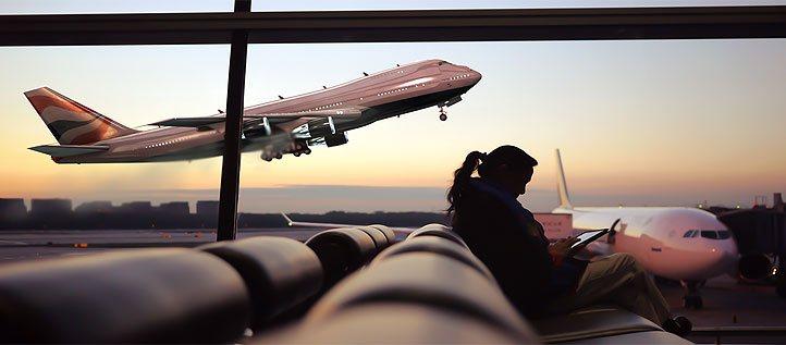 Aus dem Wartebereich eines Flughafens sichtbar hebt ein Flugzeug ab.