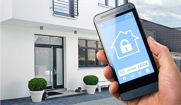 Ein Smartphone mit einer Heimsteuerungs-Applikation vor einem Einfamilienhaus